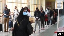 FILE - Travelers wearing masks walk at Jomo Kenyatta International Airport in Nairobi, Aug. 1, 2020. Kenyan officials have raised suspicions over the deaths of 89 Kenyans, most of them domestic workers, in Saudi Arabia.
