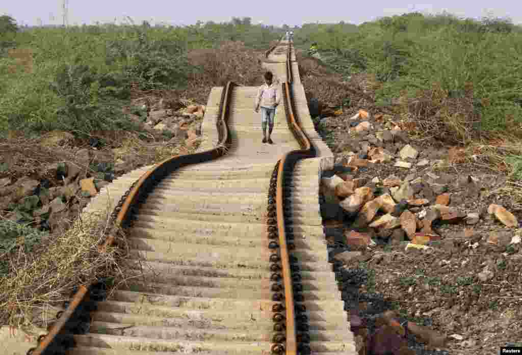 A villager walks on a railway track that was damaged after heavy monsoon rains near Patdi village in Gujarat, India.