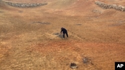 Farmer Lu Keshuang turns the soil of his drought-affected field located 80 kilometres north of Beijing. The drought could impact world wheat prices.