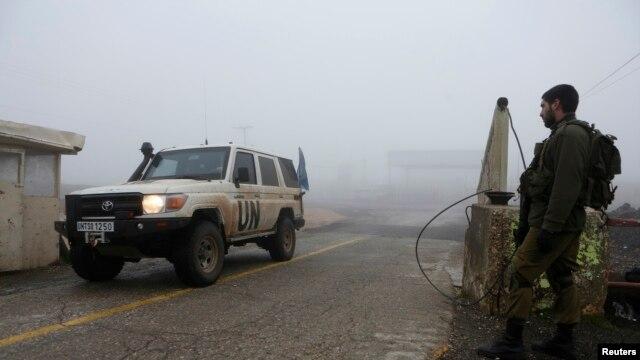 Seorang tentara Israel mengamati mobil pasukan penjaga perdamaian PBB di perbatasan Quneitra antara Israel dan Suriah di Dataran Tinggi Golan (foto: dok).
