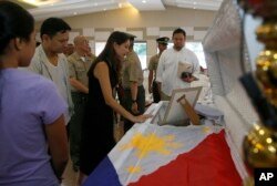 Philippine Senator Sonny Angara, second from left, and his wife, Elvira, pay their respects to Philippine Marine Pfc. Marvin Gomez, killed in the fighting with Muslim militants in Marawi City in southern Philippines, June 13, 2017 in Taguig city, east of Manila, Philippines.