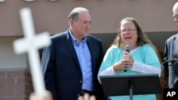 Rowan County Clerk Kim Davis, with Republican presidential candidate Mike Huckabee, left, at her side, speaks after being released from the Carter County Detention Center in Grayson, Kentucky, Sept. 8, 2015. (AP Photo/Timothy D. Easley)