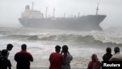 Warga menyaksikan kapal Pratibha Cauvery, yang kandas akibat hantaman topan Nilam di pantai Teluk Benggala, Chennai, India selatan (31/10).