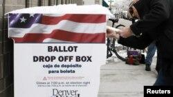 Seorang warga di Denver, Colorado, memasukkan kertas suara pada pemilu yang diadakan lebih awal (25/10). (Reuters/Rick Wilking)