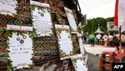 """Kartu Natal bertuliskan """"Tahun 2020 Segel Gereja Kami Dibuka"""" dipajang di antara pesan-pesan lainnya dalam kebaktian Natal oleh umat Kristiani di depan Istana Presidenan, di Jakarta, 25 Desember 2019. (Foto: AFP)"""