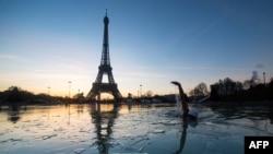 Seorang pria berenang di kolam air mancur Trocadero di depan Menara Eiffel di Paris (6/1). (AFP/Olivier Morin)