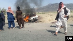 FILE - Local residents gather around a burning vehicle hit by a U.S. drone strike, May 21, 2016, near Dalbandin, Pakistan. Afghan Taliban leader Mullah Mansoor was killed in the strike. Kabul accuses Islamabad of clandestinely supporting the Afghan Taliban.