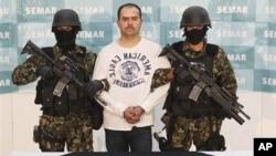"""Mexican Marines link arms with Sergio Antonio Mora Cortes, alias """"El Toto,"""" as they present him to the press after his arrest in Mexico City, Feb. 28, 2011"""