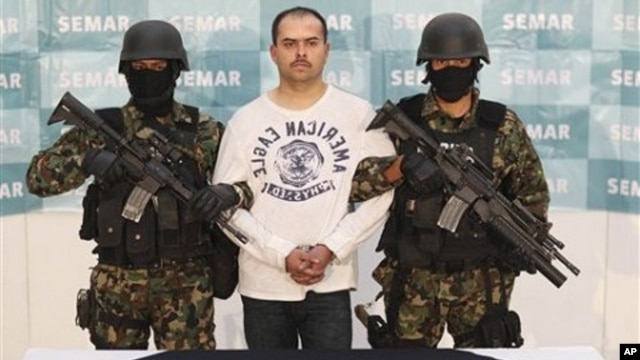 "Mexican Marines link arms with Sergio Antonio Mora Cortes, alias ""El Toto,"" as they present him to the press after his arrest in Mexico City, Feb. 28, 2011"