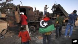 人们在查看被联军炸过的忠于卡扎菲部队的武器