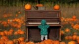 A child plays with a piano as people pick pumpkins at The Pop Up Farm ahead of Halloween, in Flamstead, St Albans, Britain.