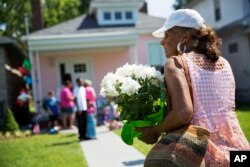 A mourner carries flowers to leave at the childhood home of Muhammad Ali, June 5, 2016, in Louisville, Kentucky.