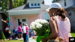Betty Sue Griffin, right, carries flowers to leave at the childhood home of Muhammad Ali, rear, Sunday, June 5, 2016, in Louisville, Ky. Ali, the magnificent heavyweight champion whose fast fists and irrepressible personality transcended sports and captivated the world, died Friday at the age of 74. (AP Photo/David Goldman)