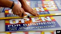 """Tom Cushing, a production expert at Fast Signs, cuts down a sheet of anti-Senate Bill 1062 signs that read """"Open for Business to Everyone,"""" in Phoenix, Arizona, Feb. 26, 2014."""