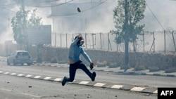 Un Palestinien lance une pierre lors d'affrontements avec les forces de sécurité israéliennes dans la ville de Bethléem, Cisjordanie, 31 mars 2018.