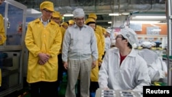 Apple Chief Executive Officer Tim Cook (L) visits the iPhone production line at the newly built Foxconn Zhengzhou Technology Park in Zhengzhou, Henan province, China, March 28, 2012 handout photo.