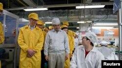 CEO Apple Tim Cook (kiri) dalam kunjungan ke Taman Teknologi Foxconn Zhengzhou di Henan, Tiongkok. (Foto: Handout)