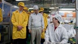 Tim Cook, izquierda, visita una línea de producción de iPhone en China. Un modelo de Mac será fabricado en Estados Unidos.