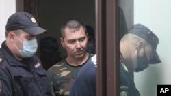 Alexander Popov, tersangka pembunuhan mahasiswi asal AS, Catherine Serou, dikawal oleh polisi ke ruang sidang di pengadilan di Kota Gorodets, barat laut Nizhny Novgorod, Rusia, Minggu, 20 Juni 2021.