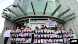 Демонстранти тримають фото своїх родичів, загиблих у квітні під час маршу проти Кунмарбека Бакієва