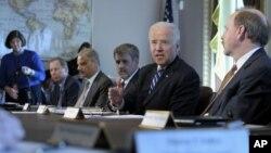 El presidente Joe Biden, segundo desde la derecha, habla ante grupos de tiradores deportivos.