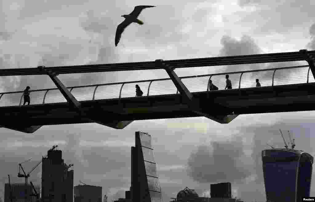 Workers cross the Millenium Bridge with the City of London in the background, Britain.