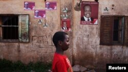 A child walks past posters for political candidates plastered on a house in Bamako, July 22, 2013.