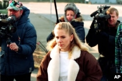 U.S. figure skating champion Tonya Harding is followed by media as she walks from an apartment in Beaverton, near Portland, Ore., to her truck on Feb. 6, 1994.