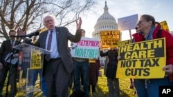 Sen. Bernie Sanders, I-Vt., joins protesters outside the Capitol as Republicans in the Senate work to pass their sweeping tax bill.