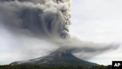 Gunung Sinabung memuntahkan abu vulkanik setinggi delapan kilometer, terlihat dari kawasan Tiga Pancur, Sumatra Utara (18/11).