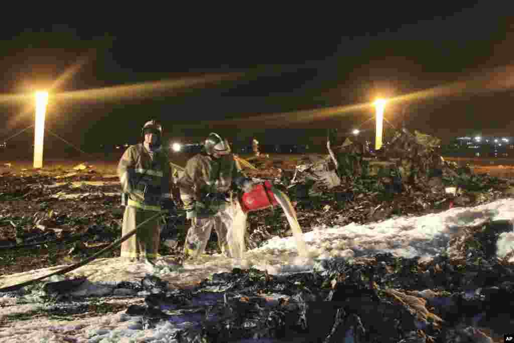 In this photo provided by Russian Emergency Situations Ministry, fire fighters and rescuers work at the crash site of a Russian passenger airliner near Kazan, the capital of the Tatarstan republic, about 720 kilometers (450 miles) east of Moscow, Nov. 17, 2013. The airliner crashed while trying to land at the airport in the city of Kazan, killing all people aboard, officials said.