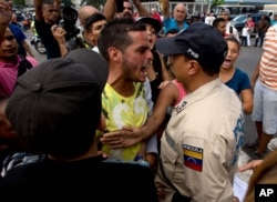 A man waiting in line at a grocery store argues with a Bolivarian National Police officer as he and others wait for food to arrive to the store in Caracas, Venezuela, June 8, 2016.