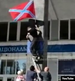 Rebels raise the DNR flag on the campus of Donetsk National University in September of 2014.