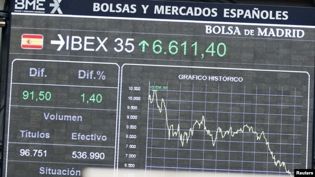 A clock stands in front of electronic boards at the Madrid stock exchange, June 19, 2012.