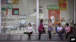 지난 25일 북한 평양 시내의 백화점 쇼윈도 앞에 시민들이 앉아있다. 쇼윈도 안에는 주방용품과 식기가 전시돼있다.