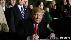 Presiden AS Donald Trump menandatangani RUU anggaran pertahanan 2020 di pangkalan udara Andrews, Maryland, Jumat (20/12).