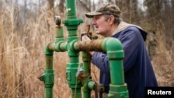 Hanson Rowe, a landowner who blames a leaky gas well on his property for health problems, smells for the odor of gas emanating from an abandoned well on his property in Salyersville, Kentucky, U.S., February 28, 2020. (REUTERS/Bryan Woolston)