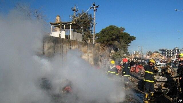 Para petugas pemadam kebakaran mencoa memadamkan api yang berkobar pasca ledakan bom di Kirkuk, 290 kilometer sebelah utara Baghdad, Irak, 3 Februari 2013. (AP Photo/Emad Matti)