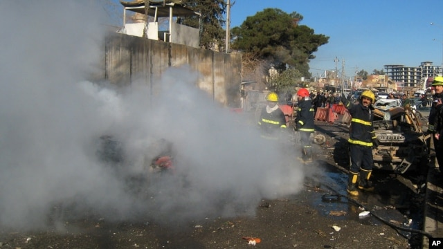 Iraqi firefighters distinguish a fire at the scene of a bomb attack in Kirkuk, 180 miles (290 kilometers) north of Baghdad, Iraq, February 3, 2013.