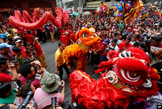 Dragon and lion dancers perform before a huge crowd in celebration of the Chinese Lunar New Year, Feb. 8, 2016 at Manila's Chinatpwn district in Manila, Philippines.