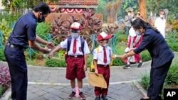 Petugas memeriksa suhu tubuh siswa sebuah SD di Jakarta, pada hari pertama sekolah dibuka kembali, 30 Agustus 2021. (AP Photo/Dita Alangkara)