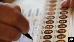 Seorang warga mengisi surat suaranya di sebuah TPS di Wellsville, Kansas (6/11). Data pendahuluan jajak pendapat nasional menunjukkan 73 persen warga AS keturunan Asia memilih Obama sebagai Presiden.