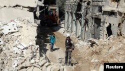 FILE - Civil defense members and men inspect a site damaged after an airstrike in the besieged rebel-held al-Qaterji neighborhood of Aleppo, Syria, Oct. 11, 2016.