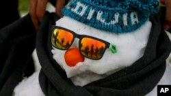 A man wraps a scarf on a snowman decked out with sunglasses, a knitted cap and an orange serving as a nose, as others play in a snow-covered park in Santiago, Chile, July 15, 2017.