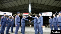 Newly graduated airmen hand over their flag to the next class during a graduation ceremony at Al-Hurria airport in Kirkuk, 250 km (155 miles) north of Baghdad, Feb.1, 2010.