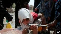 Seorang anak perempuan meminum air dari sumur yang diduga sudah tercemar bakteri kolera di pinggiran kota Sanaa, Yaman. (Foto:dok)
