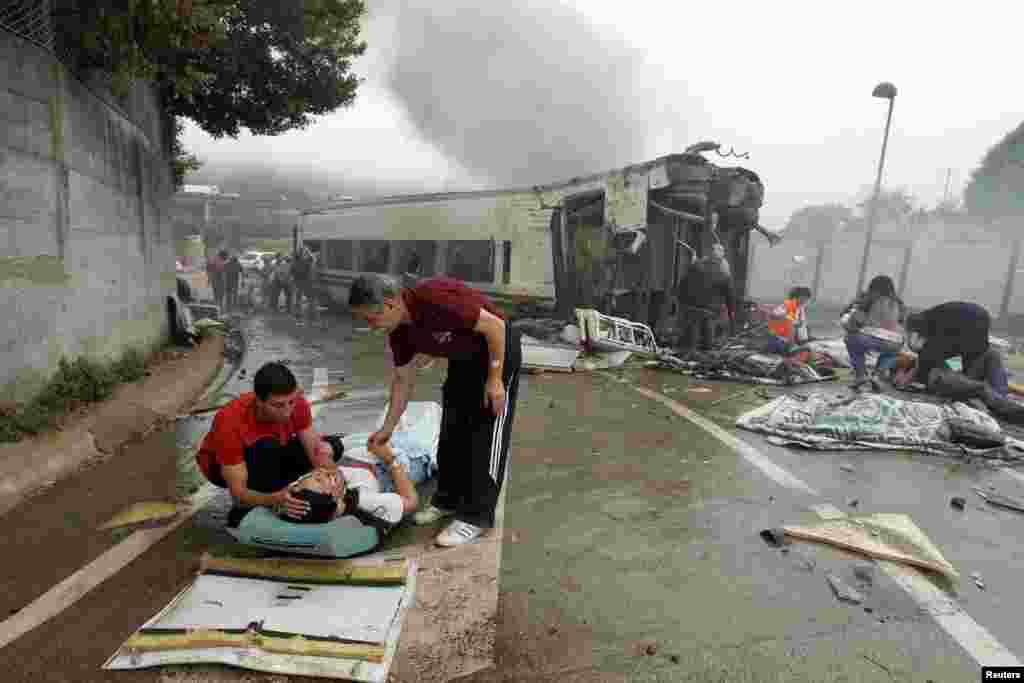 Victims receive help after a train crashed near Santiago de Compostela, northwestern Spain, July 24, 2013. At least 77 people died and score more were injured.