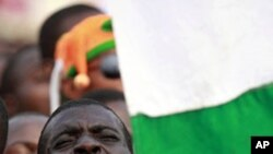 A supporter of Ivory Coast's incumbent leader Laurent Gbagbo sings the national anthem during a rally in Abidjan, 29 Dec 2010