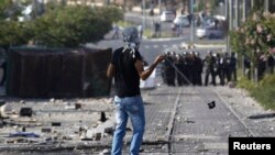 Seorang pemuda melempar batu ke arah polisi Israel ketika terjadi bentrokan sesudah shalat Jumat di daerah pemukiman Arab, di Shuafat, Israel (4/7/2014).