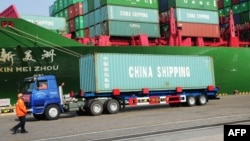 FILE - A truck transporting a container leaves the port of Qingdao, in northeast China's Liaoning province.